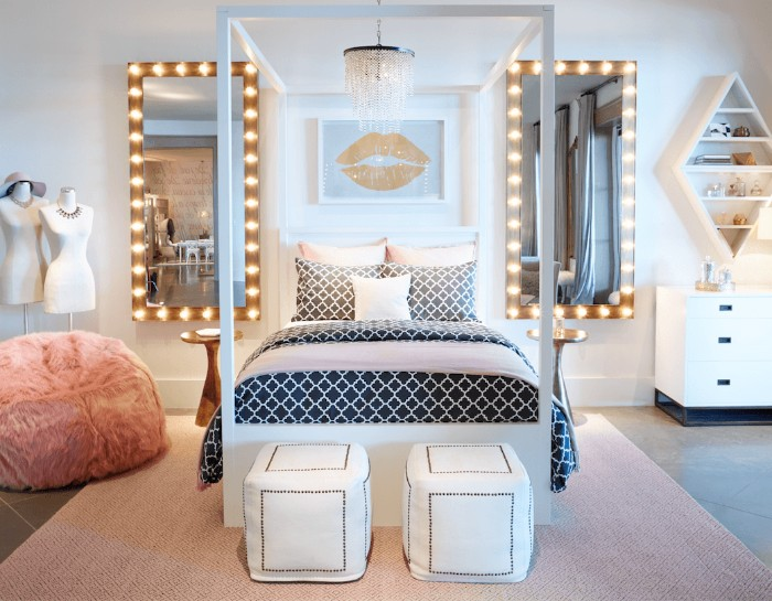 mirrors with illuminated frames, surrounding a bed, with a white frame, and black and white bedding, cool beds for teens, beige rug and a fluffy pink ottoman