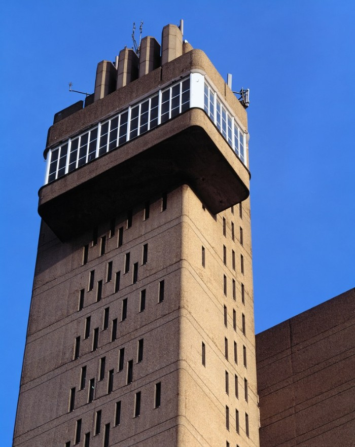 trellick tower in london england, tall structure in pale beige, with multiple narrow rectangular windows, and a balcony-like structure, concrete architecture