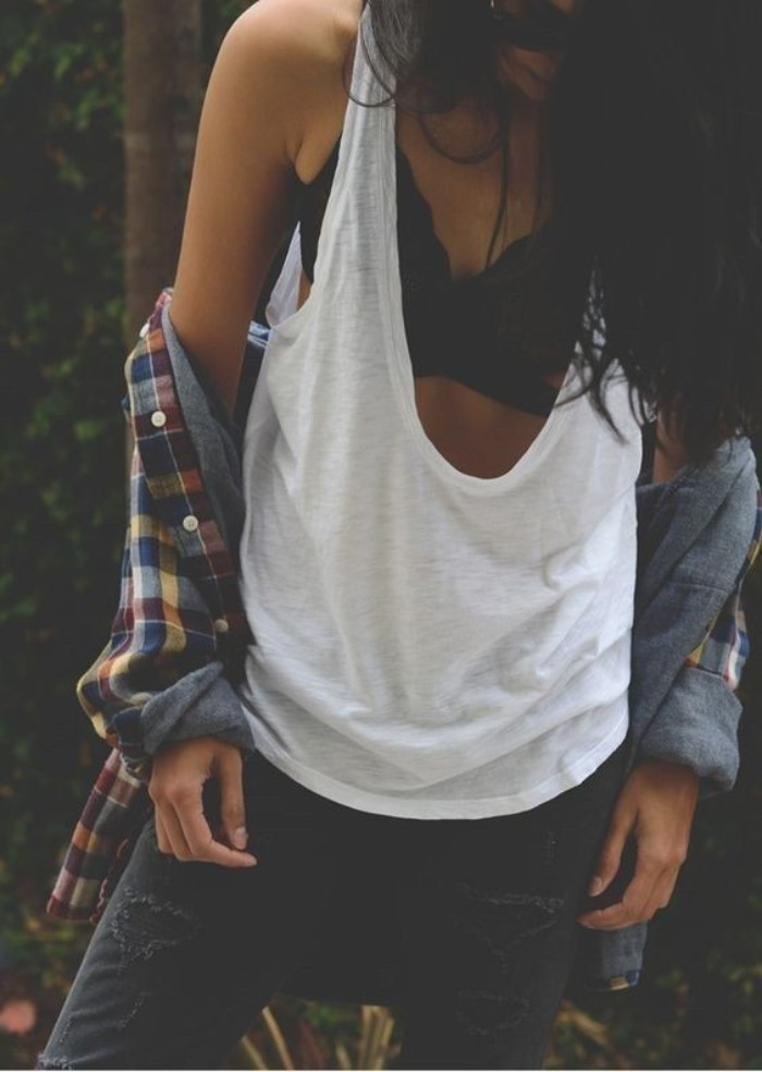 flannel shirt worn off the shoulders, by a slim woman, in a loose white tank top, over a black bralette, dark grey jeans