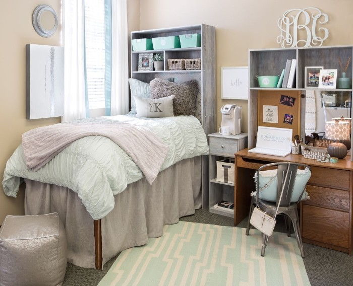 tall single bed, with pale beige, white and light pink bedding, cool beds for teens, in a room with cream walls, a wooden desk, and a grey chair
