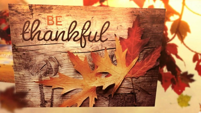 rectangular piece of wood, decorated with orange and red fall leaves, bearing the inscription be thankful, written in orange and dark brown