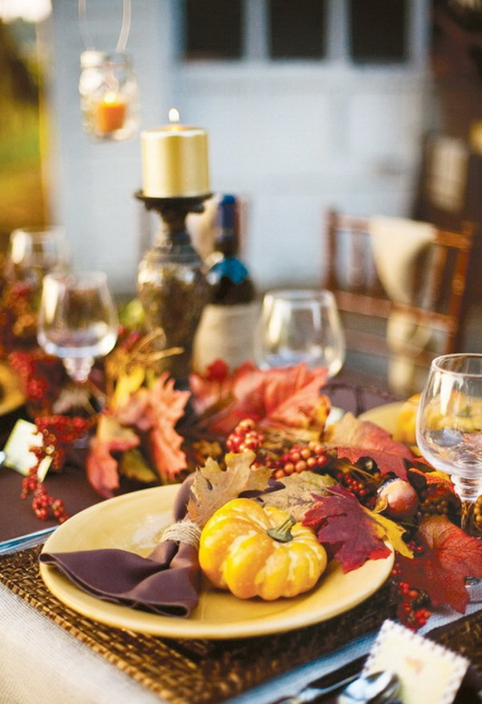 burgundy red and orange, yellow and beige fall leaves, on a table with wine glasses, a gold-colored lit candle, and a yellow plate, containing a small yellow pumpkin