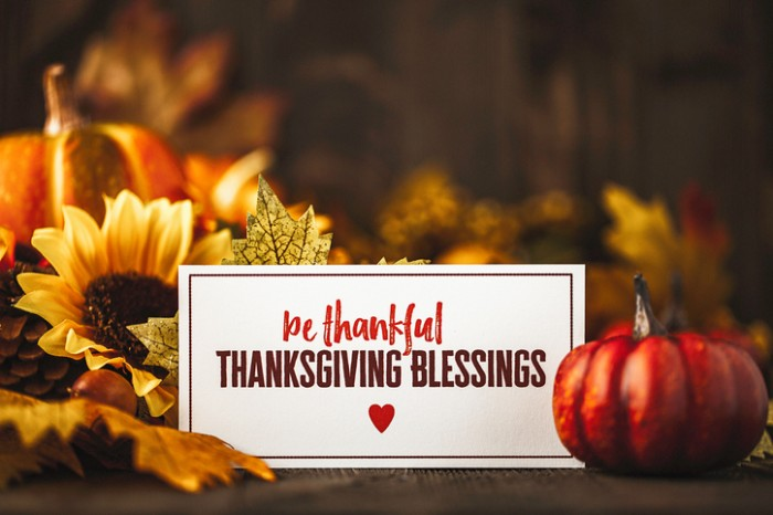 be thankful thanksgiving blessing, written in red and dark brown, on a white card, surrounded by small pumpkins, fall leaves and a sunflower, thanksgiving greetings
