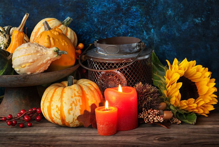 thanksgiving card messages, old metal lantern, near two lit candles, a sunflower and a selection of small pumpkins and gourds