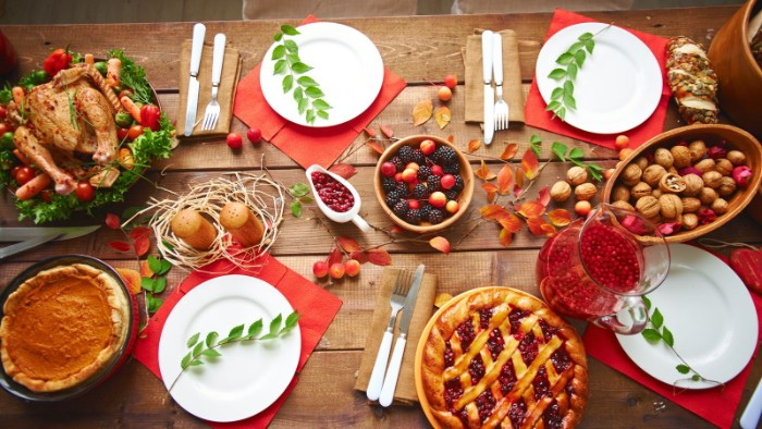 berries and walnuts, in wooden bowls, a roasted turkey and two pies, on a rustic wooden table, set for four, thanksgiving text messages with photos