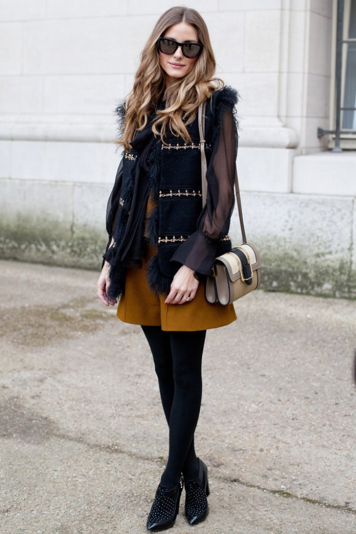 mustard yellow shorts, worn with black opaque tights, a sheer black blouse, and a black fur trimmed gilet, thanksgiving outfits
