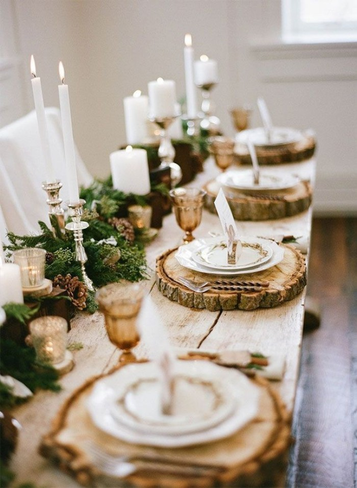 circular wooden place mats, with natural bark, placed on a rustic wooden table, decorated with green foliage, and lit white candles, in different sizes