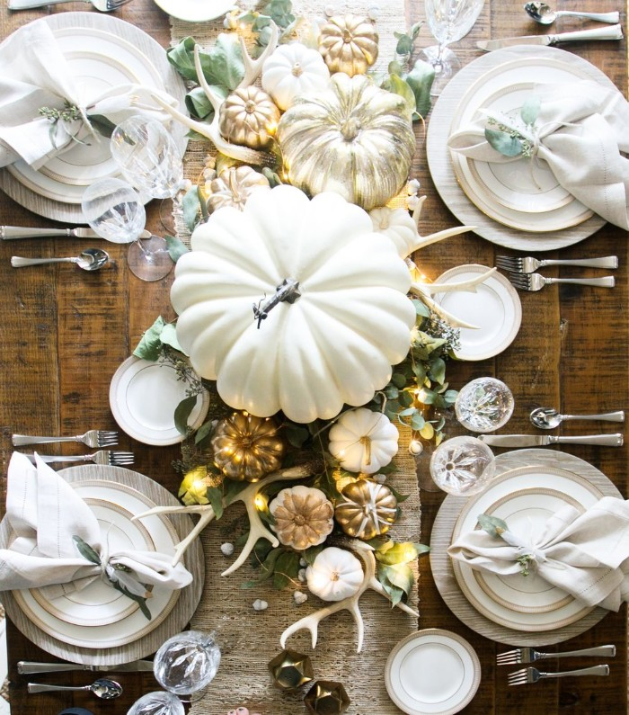 antlers and fake pumpkins, spray-painted in white, gold and silver, thanksgiving table decorations, on a dark brown, wooden table with white plates, napkins and silver cutlery