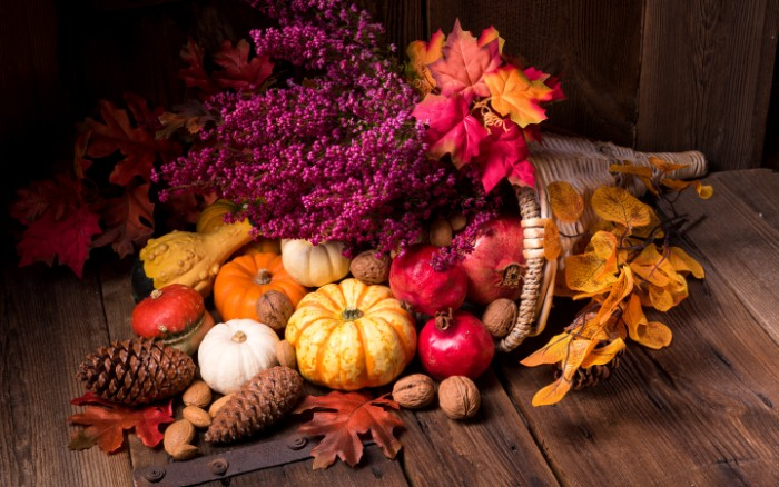 purple flowers and pomegranates, small pumpkins and pine cones, fall leaves and walnuts, spilling out from a rattan decoration, shaped like a horn