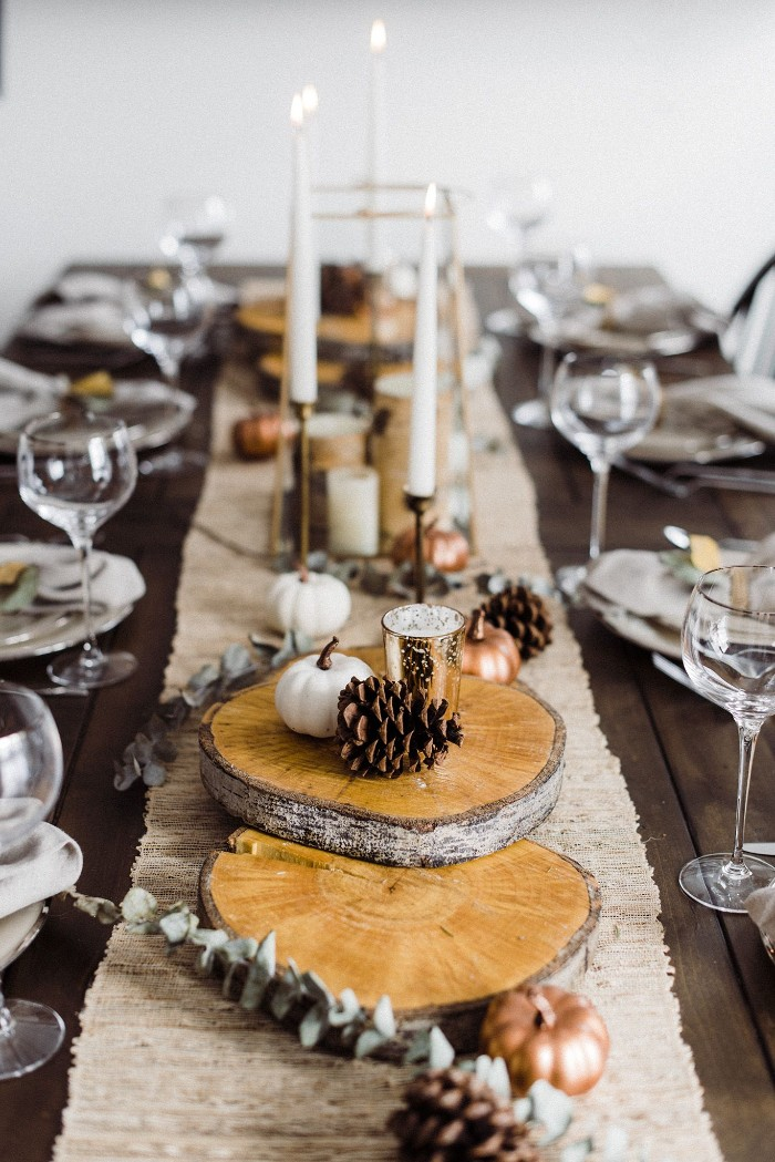 rectangular table set up for a festive meal, thanksgiving greetings, center piece featuring natural wood pieces, pine cones and small decorative pumpkins, tall lit candles