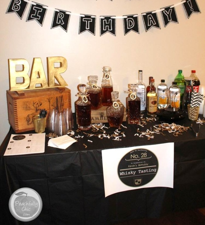 bar written in large gold letters, on top of a wooden crate, placed on a rectangular table, with a black tablecloth, and a variety of different bottles, 50th birthday celebration ideas for husband, whiskey tasting experience