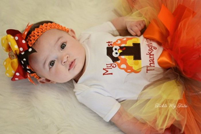 turkey cartoon in yellow, orange and dark brown, printed on a white onesie, worn with a fluffy tulle tutu skirt, in yellow and orange and brown, baby girl thanksgiving outfit, orange headband with three multicolored bows