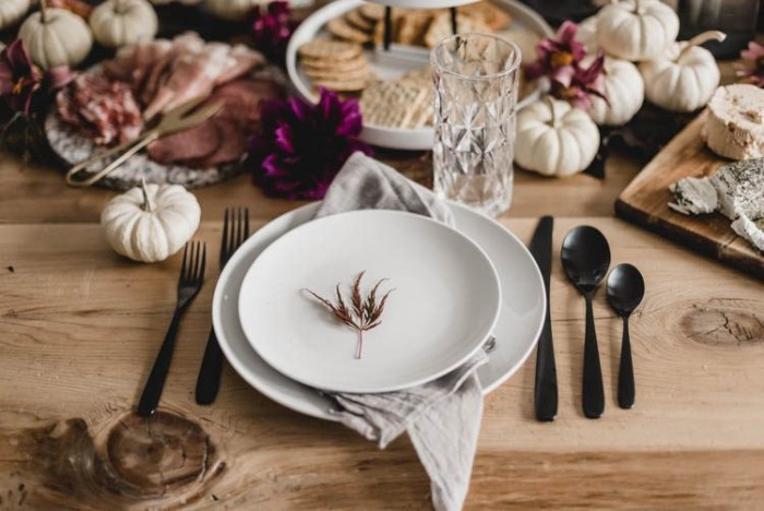 little fall leaf, placed in the middle of a round white plate, surrounded by black cutlery, on a wooden table, with various foods, and small white decorative pumpkins, thanksgiving table setting