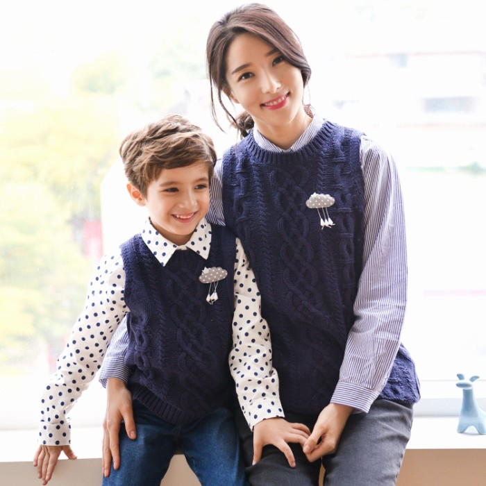 son and mother, sitting side by side, dressed in similar outfits, patterned shirts in white and dark blue, identical navy cable knit vests, with matching pins, and blue jeans