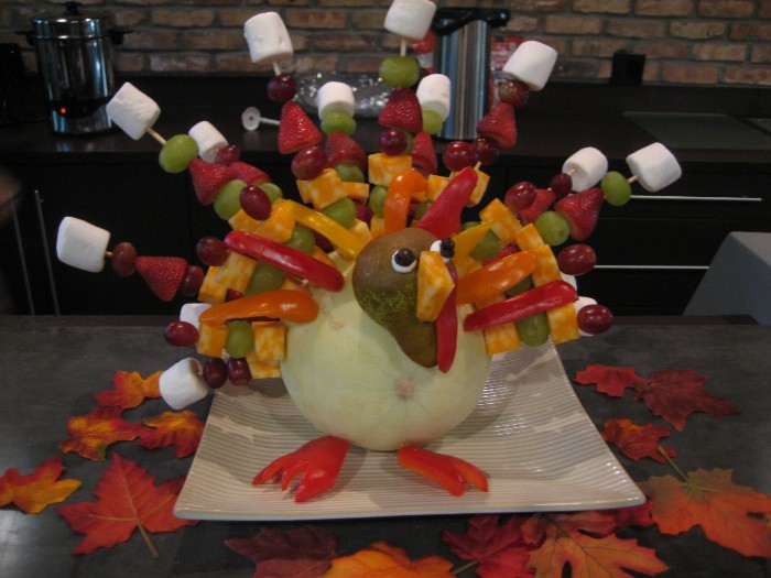 marshmellow and fruit kaboobs, pinned on a pale pumpkin, made to resemble a turkey, with fruit and vegetables, turkey decorations, on a large white square plate, surrounded by fall leaves