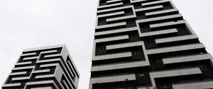 identical buildings with maze-like decorative elements, brutalist design, seen side by side on a black and white photo