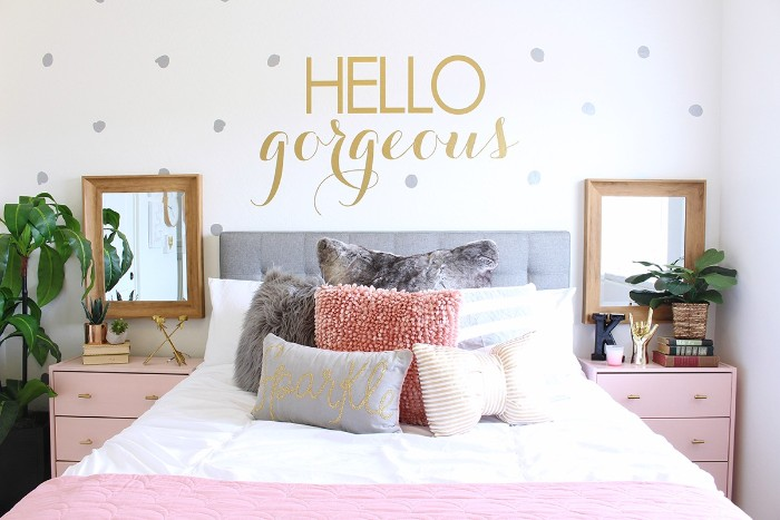 hello gorgeous written in gold, on a white wall, decorated with silver dots, teen bedrooms, symmetrical set up, with a bed covered in cushions, and surrounded by two mirrors