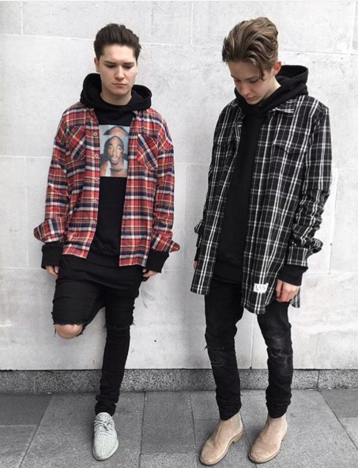 a pair of guys, standing side by side, dressed in black, ripped skinny jeans, and plaid shirts in different colors, over black hoodies