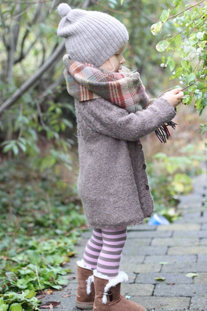 toddler thanksgiving outfit, grey cardigan and a plaid blanket scarf, striped leggings in pale pink and dark purple, beige shearling fur boots, and a light grey beanie hat