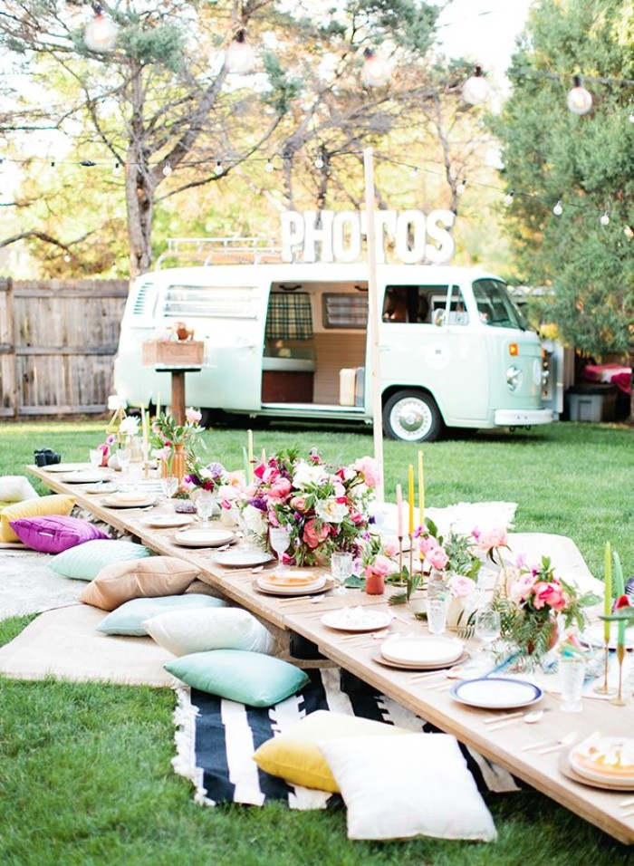 boho style garden party, with a low wooden table, set for a festive meal, with plates and flowers, and surrounded by blankets and cushions, 50th birthday ideas, light blue van nearby
