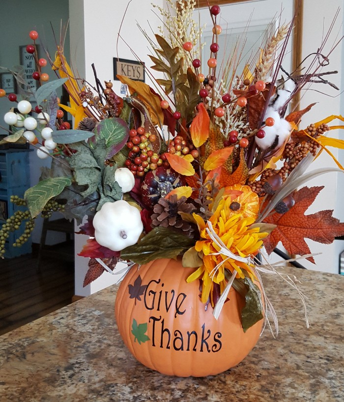 plastic orange pumpkin, with the inscription give thanks, filled with faux fall leaves, pinecones and berries, cotton and wheat stalks, and many others