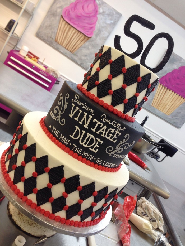 multi-layered cake in black and white, with red details, and a topper shaped like the number 50, vintage dude written in white frosting