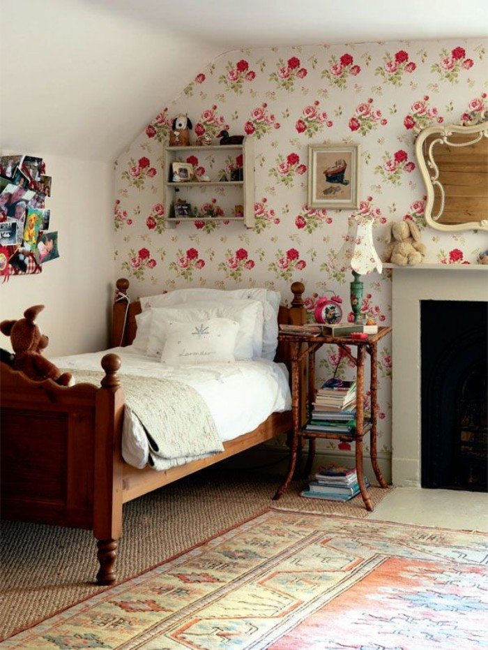 wallpaper with a floral pattern, decorating one wall of a bright room, containing a vintage style wooden bed, cool beds for teens, fireplace and an ornamental rug