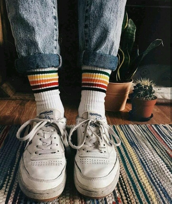well-worn white, retro lace-up sneakers, worn with tennis socks, featuring multicolored stripes, 90s grunge items, acid wash ankle jeans