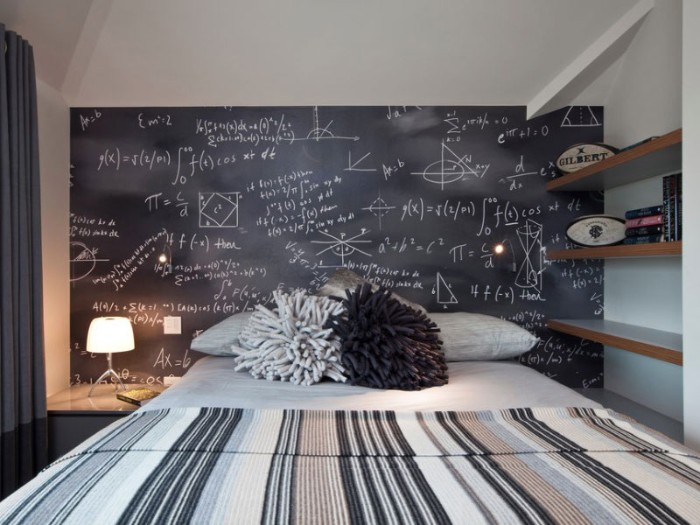 blackboard covered in mathematical equations, written in white chalk, on one of the walls of a room, with a bed in grey and white, teenage bedroom ideas for small rooms