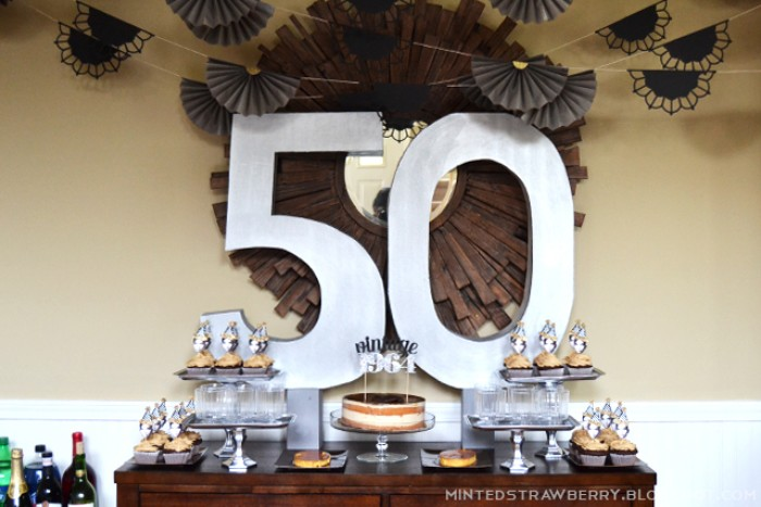 big wall decoration, featuring the numbers 5 and 0, surrounded by grey, fan-like paper garlands, near a table with a large cake, and some cupcakes, 50th birthday celebration ideas for husband