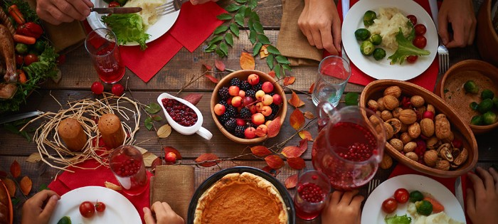 table set for four, white plates filled with vegetables, jug of red juice and glasses, walnuts and berries in wooden bowls, thanksgiving messages for friends, rustic table decor