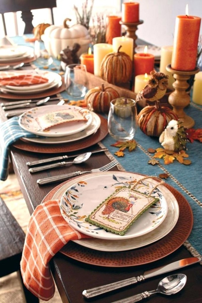 place holder cards, with colorful turkey illustrations, on top of stacked plates, on a table decorated with lit, yellow and orange candles