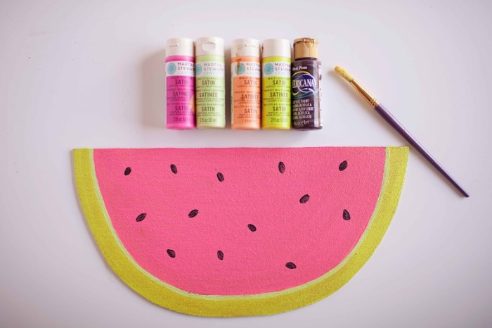 five bottles of paint, and a used paint brush, placed near a piece of cork, painted to look like a slice of watermelon, cheap ways to decorate a teenage girl's bedroom, customized bulletin board