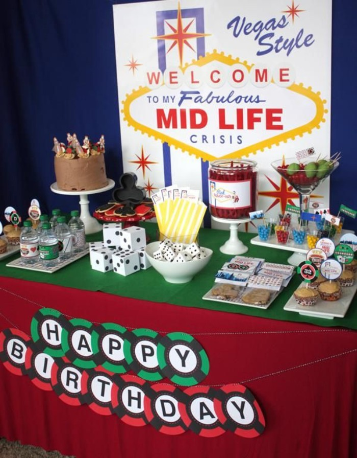 snack table with casino-themed canapes, decorated with a large poster, resembling the las vegas sign, reading welcome to my fabulous mid life crisis, 50th birthday party ideas for men, with lots of humor