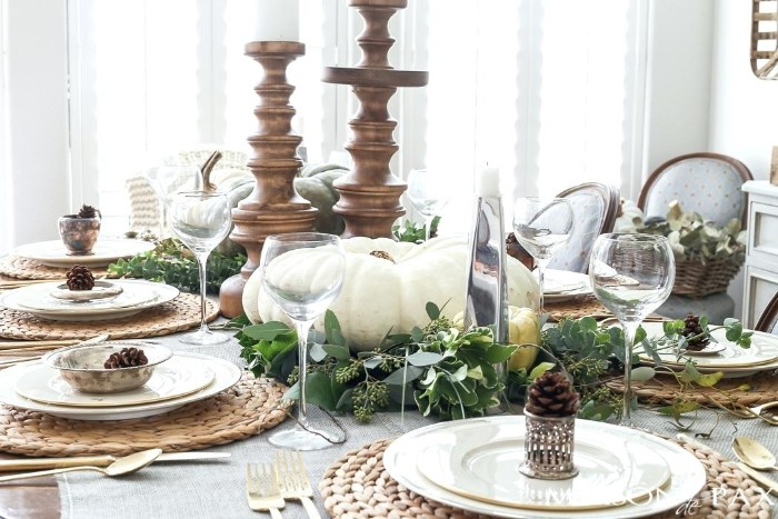 round knitted rattan table mats, white plates and wine glasses, on a table, decorated with wooden candleholders, green leaves and pinecones, thanksgiving table decorations, large white pumpkin