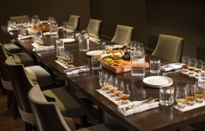 long wooden table, set for ten people, with five small glasses in front of each chair, 50th birthday party ideas, whiskey tasting with fruit and cheese