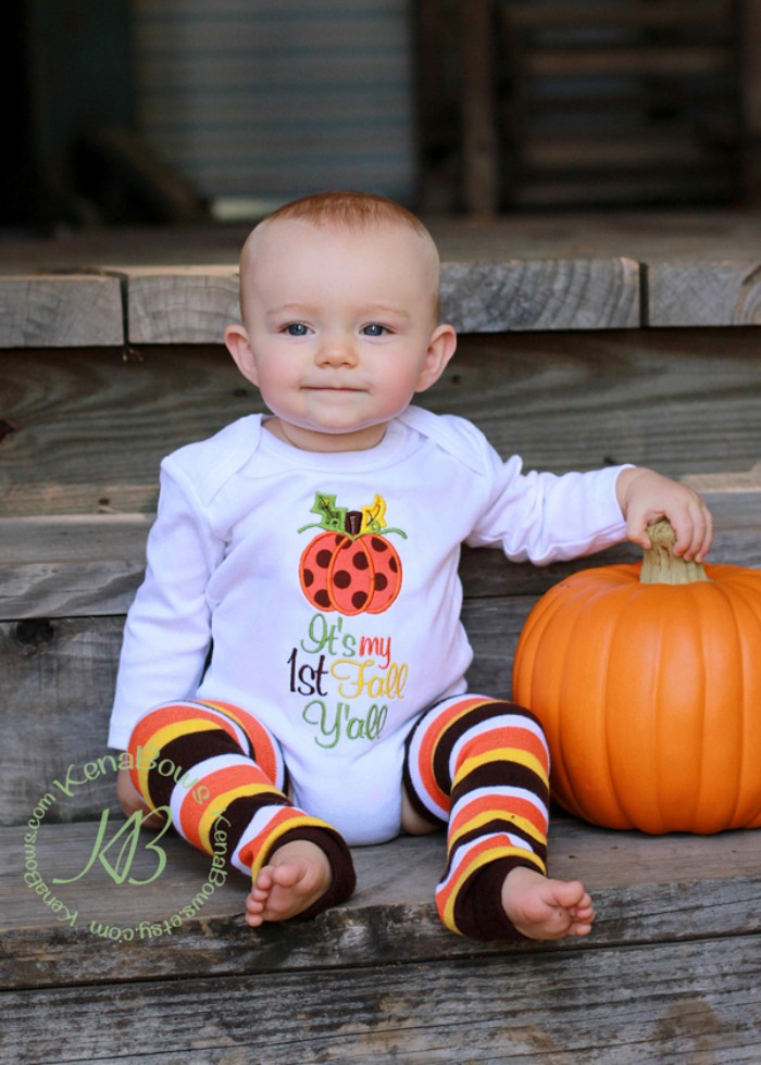 it's my first fall y'all, and an image of a pumpkin, printed in different colors, on a white onesie, worn by a baby in striped leggings, baby's first thanksgiving outfit, orange faux pumpkin nearby