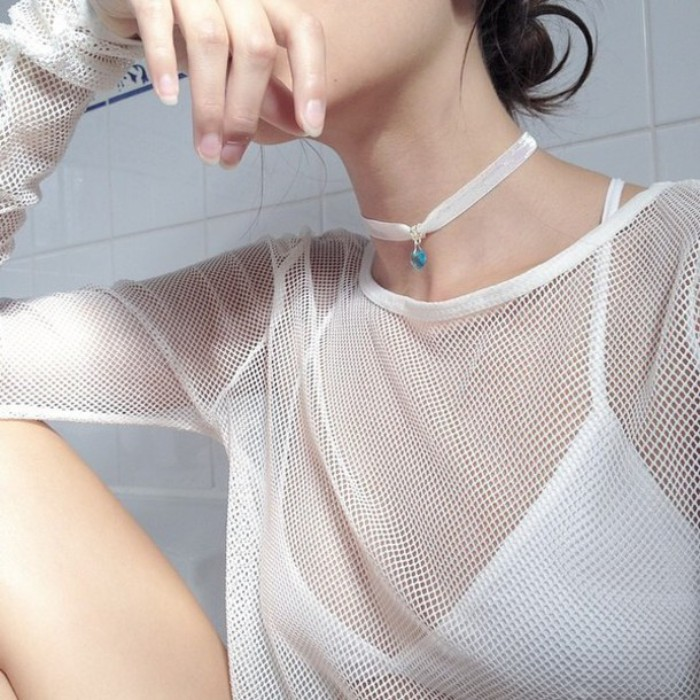 meshy sheer white top, with long sleeves, worn over a white bralette, by a pale young woman, with a white lace chocker necklace, decorated with a blue gem, 90s grunge