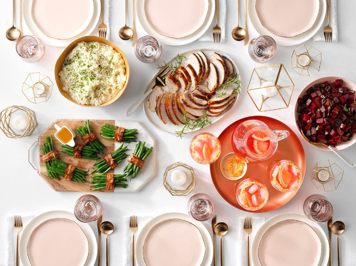 rose gold cutlery, on a table with pale pink and white plates, white tablecloth and several dishes, thanksgiving wishes, roast turkey slices, asparagus with bacon, and others