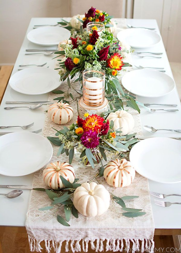 purple and red, yellow and orange flowers, with green leaves, in three bouquets, surrounded by small white pumpkins, some decorated with gold stripes, thanksgiving centerpiece, placed on a white rectangular table