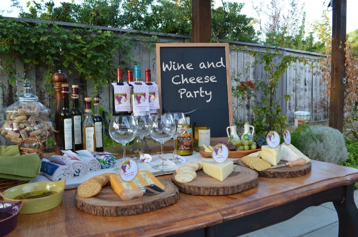 table with several cheese platters, wine bottles and glasses, small blackboard featuring the inscription, wine and cheese party, 50th birthday party ideas