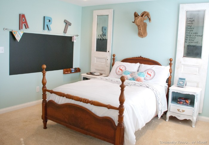 antique style bed, made of wood, and featuring white bedding, and pillows in pale pink, light blue and white, cool beds for teens, in a room with pale blue walls, decorated with a blackboard, and other items