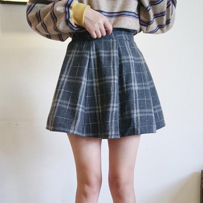 grunge definition, slim young woman, dressed in a woolen, grey plaid mini skirt, and a beige oversized jumper, with blue stripes, and yellow cuffs