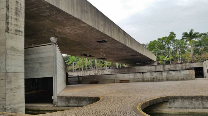 grounds of the brazilian museum of sculpture in sao paulo, yard covered in stone pavement, with a large concrete bridge overhead