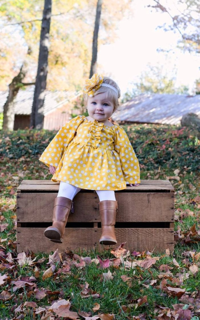 polka dots in white, on a yellow dress, with long sleeves and frills, worn by a smiling baby girl, with brown leather boots, white leggings and a yellow and white head ornaments