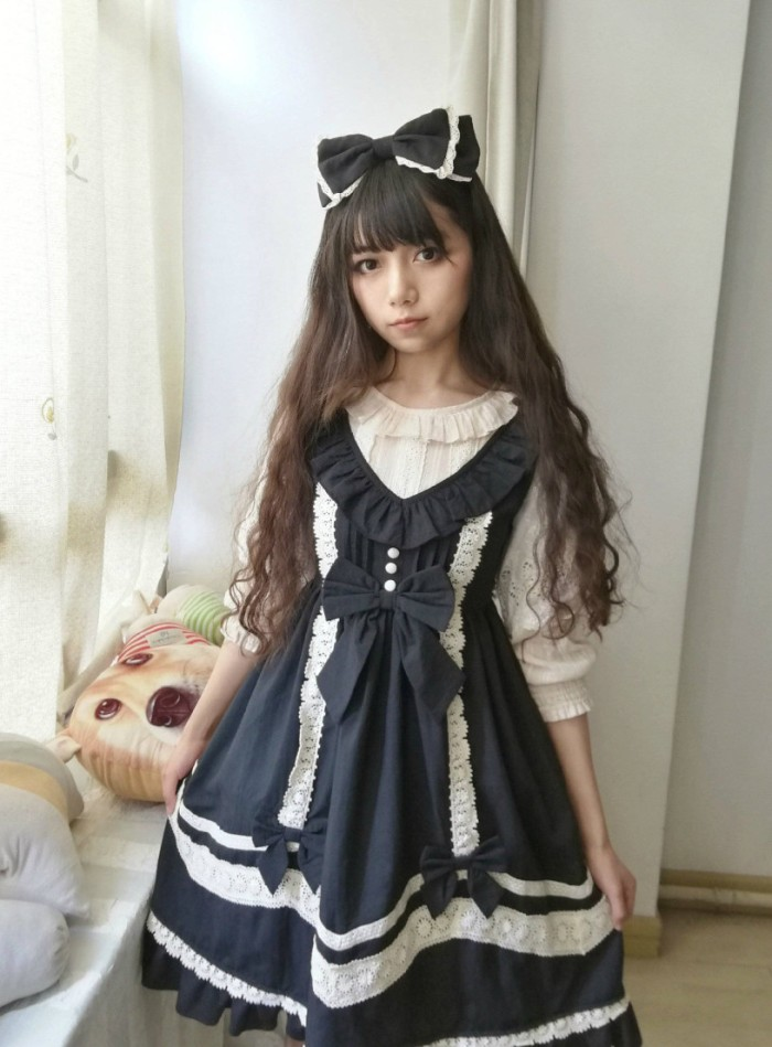 v-neck pinafore dress, in dark navy blue, featuring white lace and decorative bows, worn over a frilly white blouse, by a japanese lolita, with long dark brunette hair
