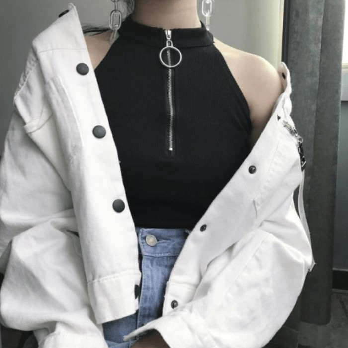 white baggy jacket, with black click-clack buttons, worn over a sleeveles black top, with a high collar, and a zip-up detail, pale blue jeans, and chain-like earrings
