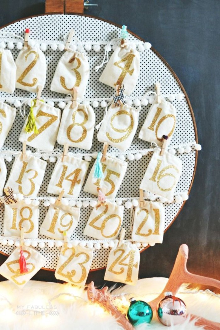 embroidery hoop with white and black fabric, decorated with 24 drawstring pouches, attached to pieces of white lace ribbon, christmas advent calendar diy idea