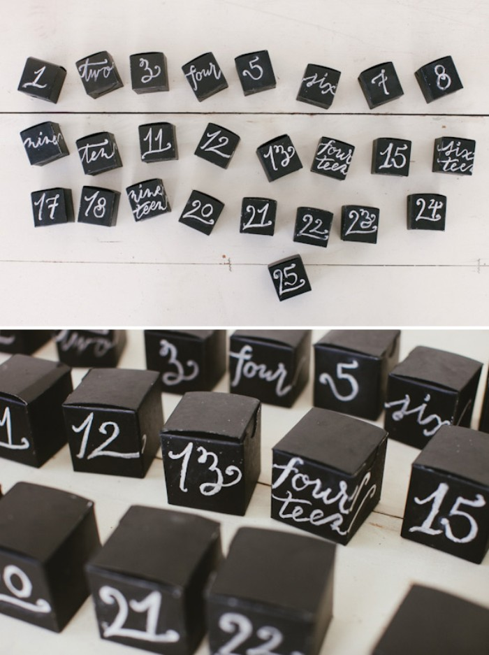 twenty five black, cube-shaped boxes, each decorated with a different number, written by hand, with white chalk, diy advent calendar, next image shows a close up of the boxes