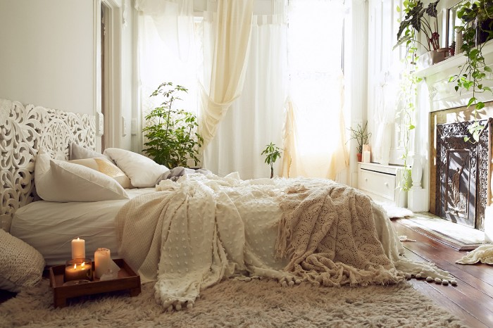double bed with white, cream and light beige pillows, linen and blankets, in a room with several green potted plants, a fireplace and a window with light curtains